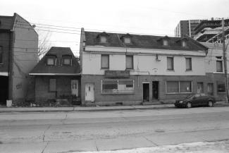 Photo noir et blanc montrant une petite maison et un dépanneur délabrés