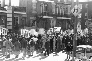 Des dizaines de personnes manifestent dans la rue en tenant des pancartes.