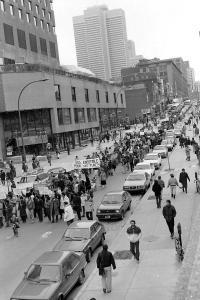 Des gens marchent dans les rues brandissant des pancartes. Des voitures sont stationnés sur la rue.