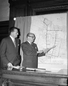 Photographie de Jean Drapeau, accompagné d'un homme, présentant un plan du métro.