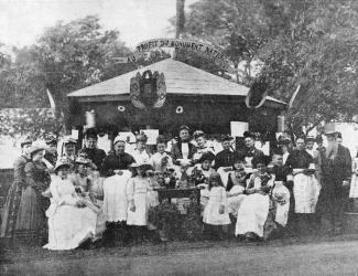 Photographie d'un groupe de gens devant un pavillon affichant «Au profit du Monument National».