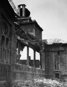 Photographie d'une paroi de l'église en démolition; des débris ornent le sol.