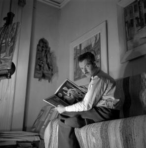 Un homme est assis, un livre dans les mains. Il se tourne pour regarder le photographe.