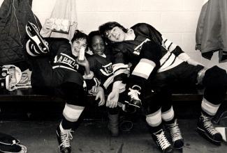 Trois jeunes hockeyeurs sont assis collés un sur l'autre sur un banc, dont un jeune Antillais au centre.