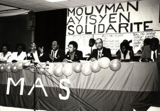 Des membres du Mouvement haïtien de solidarité sont assis derrière une table pour prendre la parole lors d'un événement