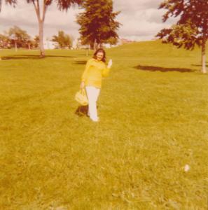 Diane Groulx de plein pied au milieu d'un grand espace vert envoie la main au photographe