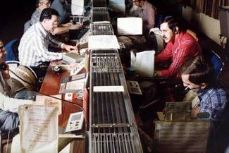 Photo couleur d'un centre de télécommunications avec une longue série de tables avec des appareils au centre. Des hommes sont assis de chaque côté.