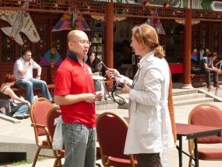 Une femme tenant un micro interviewe un homme d'origine chinoise sur une place publique dans le Quartier chinois.