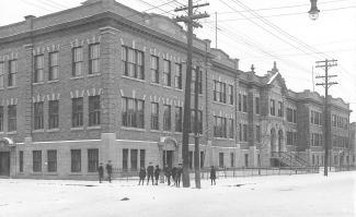 Photo noir et blanc de la façade et d'un côté d'un grand édifice à trois  étages. Neuf personnes sont debout au coin de la rue devant l'édifice.