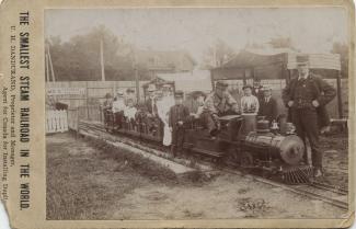 Henri-Ucal, sept ans, le fils aîné des Dandurand, se tient devant le plus petit train à vapeur du monde.