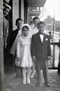 Quatre enfants habillés pour leur communion sur un balcon au 3e étage d'un triplex. Les parents sont à la porte.