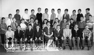 Photo en noir et blanc d'une classe de cinquième année. Il y a trois rangées d'enfants. L'enseignante est assis au milieu de la première rangée.