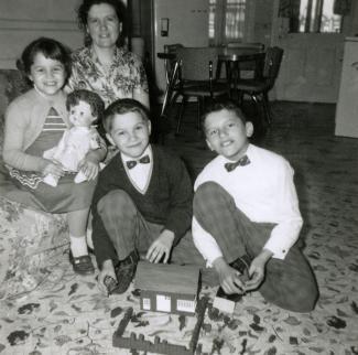 Une mère et ses trois enfants prennent la pose avec les cadeaux de Noël reçus dans leur salon. On voit la cuisine à l'arrière-plan.