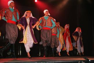 Sept artistes vêtus d'habits traditionnels se trouvent sur une scène.