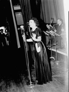 """La chanteuse Alys Roby accompagnée par un orchestre sur la scène d'une salle de spectacle lors de la radiodiffusion de l'émission \""""Tourbillon de la Gaieté\"""" de l'auteur Roger Marien par la station C.K.A.C. à Montréal."""