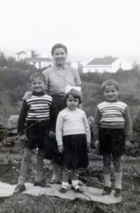 Photo en noir et blanc d'une mère et de ses trois enfants qui ont entre huit et cinq ans, dans une cour avec deux maisons en arrière-plan.