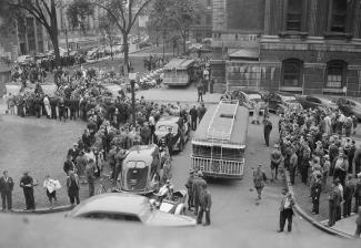 Foule massée à l'extérieur regardant passer les minibus utilisés pour transporter les Italiens au quartier général de la gendarmerie