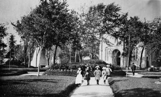Photographie en noir et blanc représentant un groupe d'enfants marchant dans un parc, avec à l'arrière-plan une église.