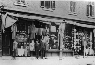 Le magasin Fineberg sur la rue Ontario. Deux hommes se tiennent debout devant l'entrée.