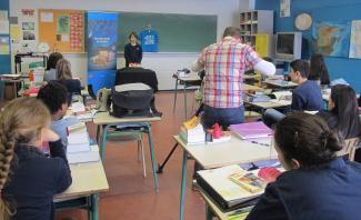 Un caméraman filme la présentation orale d'un élève du niveau secondaire sur son trésor de famille dans une classe.