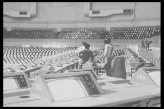 Photographie des équipements de télécommunication du stade, avec les techniciens au centre.