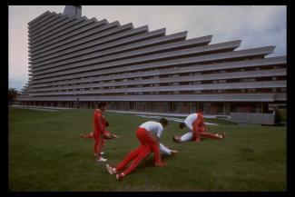 Photographie de sept athlètes vêtus de rouge et s'étirant devant un bâtiment du village des athlètes.