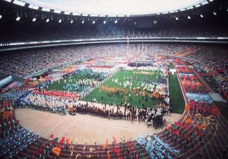 Photographie couleur du spectacle au stade olympique, avec une foule sur le terrain et la piste de course.