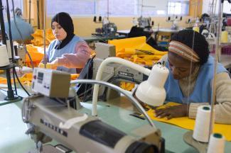 Gros plan sur deux femmes travaillant sur des machines à coudre industrielles dans un grand atelier.