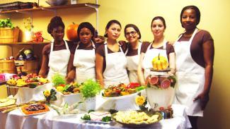 Six femmes debout prennent la pose devant une table garnie de bols et d'assiettes remplis de nourriture.