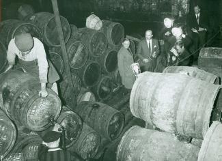 Des hommes, certains avec des appareils photo, se tiennent à droite de l'image et regardent deux autres hommes déplacer un gros baril. Le reste de la pièce est rempli de barils.