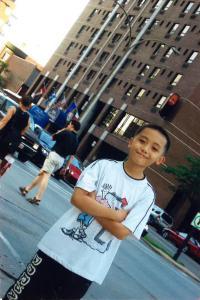 Photo d'un jeune garçon souriant les bras croisé dans une rue de Montréal. Un hôtel de plusieurs étages se trouve en arrière-plan. La photo est prise de biais.