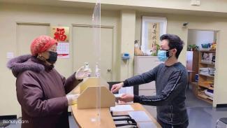 Un jeune homme et une dame, tous deux d'origine chinoise, sont de chaque côté de comptoir dans un grand bureau.