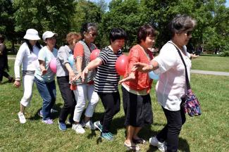 Sept femmes marchent l'une derrière l'autre dans un parc avec un ballon entre chacune qu'elles doivent faire tenir.
