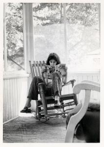 Pierre Huet lit un magazine Spirou assis sur une véranda