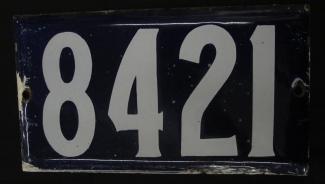 Photographie d'une plaque d'adresse rectangulaire avec les chiffres 8421 écrits en blanc sur fond bleu.