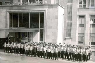 Photographie en noir et blanc d'un groupe de policiers en uniforme se tenant debout devant la porte du Montreal General Hospital.