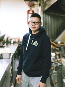 Photo couleur d'un jeune homme portant des lunettes dans la cuisine d'un restaurant.