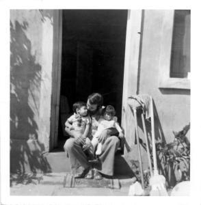 Un père et ses deux jeunes enfants assis sur le pas de la porte de leur maison au Chili