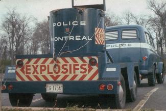 Photographie couleur montrant la partie arrière d'un camion bleu auquel est attachée une remorque sur laquelle il y a un grand contenant de métal cylindrique. Sur la porte de la remorque, il est écrit « explosifs » en lettres majuscules.