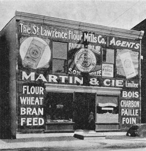 Édifice à deux étages abritant une quincaillerie avec des publicités murales sur la façade annonçant bois, charbon, paille et foin.