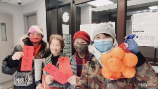 Photo couleur montrant quatre femmes d'origine chinoise dans une salle, l'une tient un sac d'oranges et deux tiennent des cartons rouges avec un texte en chinois.