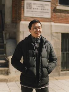 Photo couleur d'un jeune homme souriant, les mains dans les poches de son manteau, devant un édifice dans le quartier chinois.