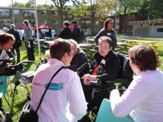 Plusieurs personnes participent à un événement dans un espace vert au centre d'unités d'habitations de trois étages. À l'avant-plan, un homme portant un sarrau blanc écoute une dame en fauteuil roulant.