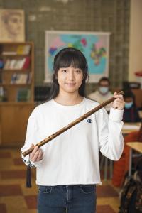 Photo d'une jeune fille d'origine chinoise tenant un objet de forme longue en bois dans une classe. L'arrière-plan est flou.