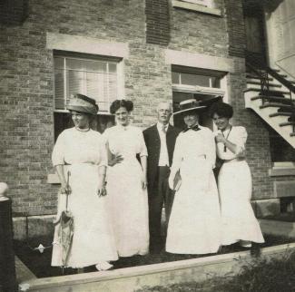 Photographie en noir et blanc représentant un homme d'âge mûr entouré de quatre jeunes femmes devant un immeuble de brique.