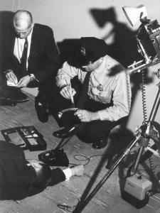 Photographie en noir et blanc, en plongée, montrant un policier passant un pinceau sur un combiné de téléphone.