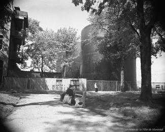 Photographie en noir et blanc d'un parc. À l'arrière-plan, un édifice à trois étages et des réservoirs à mélasse.