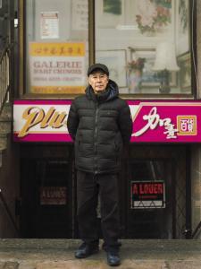 Photo couleur plein pied d'un homme âgé debout devant un édifice commercial du Quartier chinois.