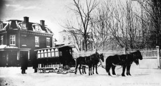 Photographie d'une voiture attelée à des chevaux, en hiver.