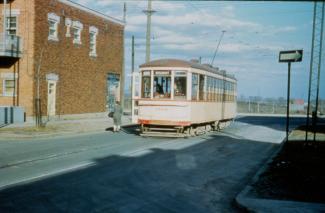 Photographie couleur d'un tramway électrique et d'un bâtiment. La devanture du wagon affiche «ROSEMONT».